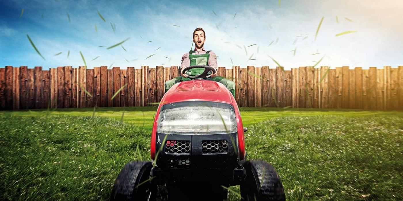 Un paysagiste conduisant un tracteur